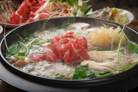 Shabu-shabu, hotpot with mushroom, chives, bok choy, vegetables and beef in pot Foto de archivo
