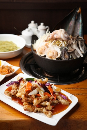 Korean cuisine Haemul-tang, spicy seafood stew with scallop, octopus, abalone and mushroom in pot served with sweet and sour pork Stock fotó