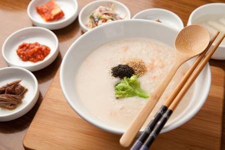 close-up shot of mung bean rice porridge,wood spoon, chopsticks and various side dish Stock Photo