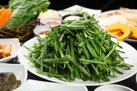 Korean side dish, chives, pickled radish, pickled sesame leaf and lettuce in basket