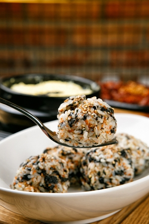 spoon scooping Jumeok-bap, rice ball with dried seaweed on plate Stock Photo