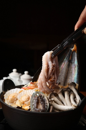 tongs holding octopus from Korean cuisine Haemul-tang, spicy seafood stew with scallop, octopus, abalone and mushroom in pot