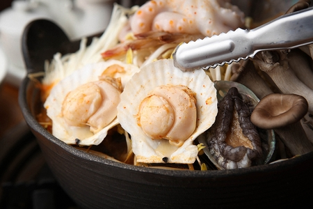 tongs holding scallop from Korean cuisine Haemul-tang, spicy seafood stew with scallop, octopus, abalone and mushroom in pot Reklamní fotografie