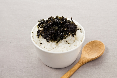 rice bowl with dried seaweed toppings, wood spoon 스톡 콘텐츠