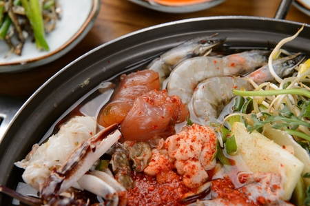 Korean cuisine Haemul-tang, spicy seafood stew with crown daisy, bean sprout, shrimp crab, fish and radish in pot