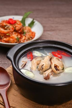 wood spoon scooping mussel soup in Ttukbaegi, earthen pot Stock Photo
