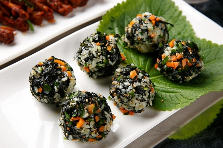 Jumeok-bap, rice ball with dried seaweed on plate with sesame leaf Stock Photo
