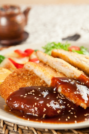 Donkatsu, pork cutlet with sauce served with lettuce salad