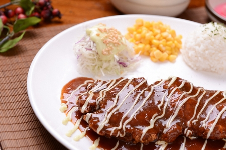 Donkatsu, pork cutlet with sauce served with lettuce salad and sweet corn