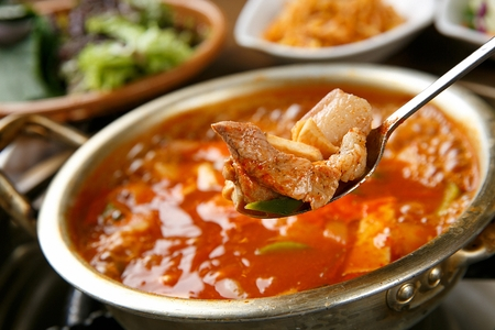 spoon scooping pork from Gochujang jjigae, soup with pork, onion and kimchi on nickel-silver pot