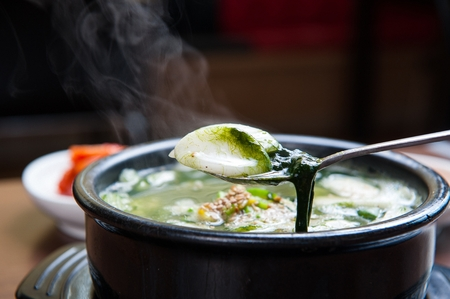 spoon scooping seaweed fulvescens soup with rice fromTtukbaegi, earthen pot
