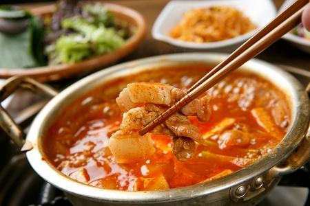 chopsticks holding pork from Gochujang jjigae, soup with pork, onion and kimchi on nickel-silver pot