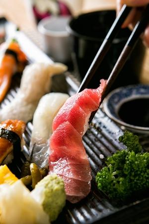 chopsticks holding salmon sushi from assorted sushi platter including shirmp, beef, salmon and flatfish sushi Reklamní fotografie - 117882354