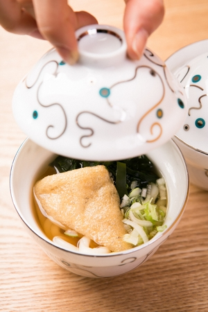mini hot udon noodles soup with spring onion, seaweed and fried tofu