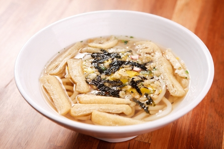 hot udon noodles soup with dried seaweed and fried tofu