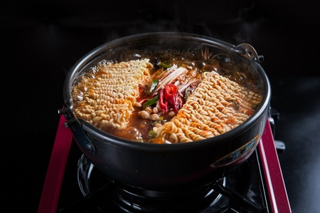 Korean-Chinese cuisine spicy Jjambbong ramyeon noodles on portable stove