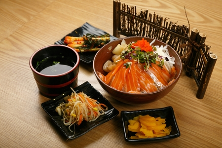 Salmon rice bowl with greens and flying fish roe served with kimchi and side dish