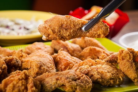 fried chicken on tongs Stockfoto