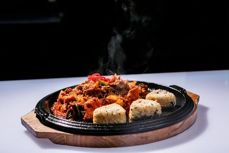 Jeyuk Bokkeum, stir fried spicy pork with vegetables and Onigiri, triangular rice ball 免版税图像