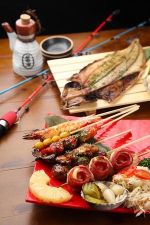 Izakaya setting, grilled fish, assorted skewers, sake and fishing rod