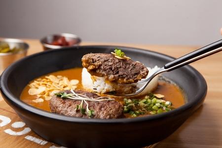 fork scooping hamburger steak with rice