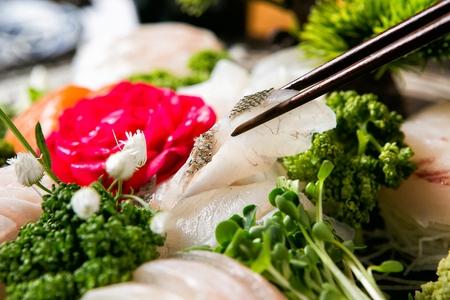 fish sashimi on chopsticks