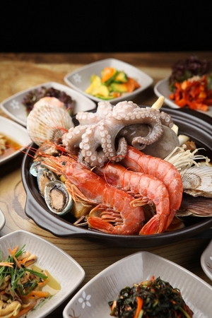 assorted steamed seafood including small octopus, shrimp, abalone and clams on pot, served with side dish