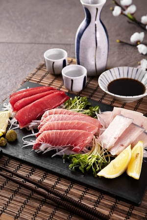tuna sashimi platter served with soy sauce and sake cups