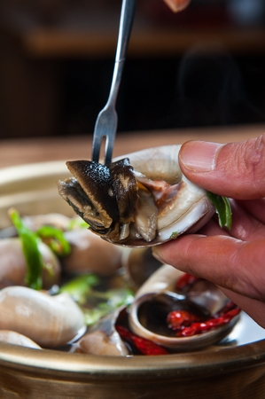 whelk on fork from steamed seafood pan with whelf and mussel Stock Photo