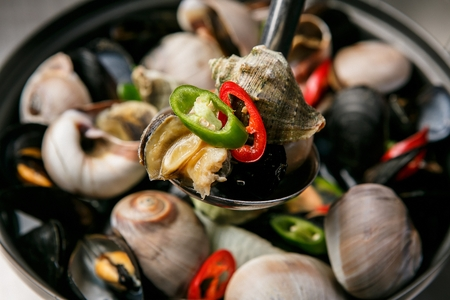 steamed seafood like whelk and mussel scooped using ladle