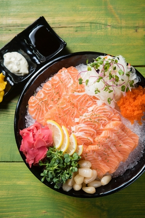 salmon sashimi decorated with sliced lemon served with shallot and ginger
