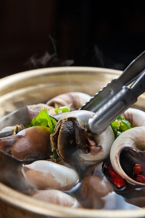 whelk soup, whelk held on tongs