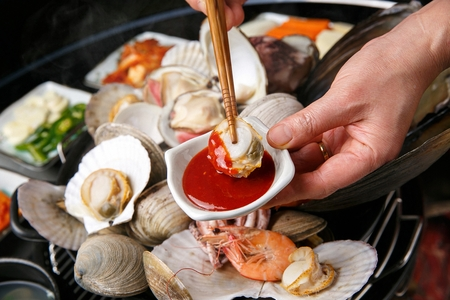dipping clam from steamed clams in pan in Chojang, spicy sauce