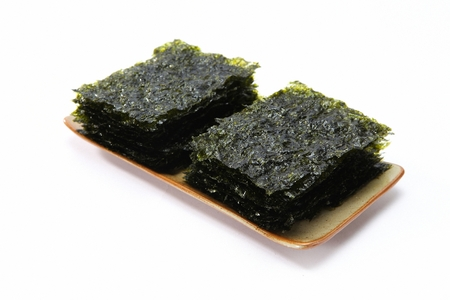 dried seaweed on wood plate, white background