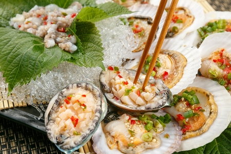 Chopsticks grabbing raw abalones with sprinkled sliced welsh onions and chili, in abalones shell Stock Photo