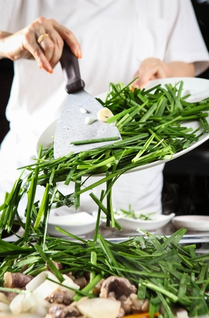 hand sprinkling chives on duck meat being grilled on grill pan
