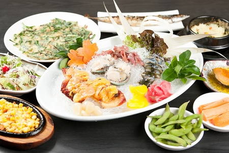 assorted seafoods like abalone, spoon worm and sea squirt on plate amd side dish