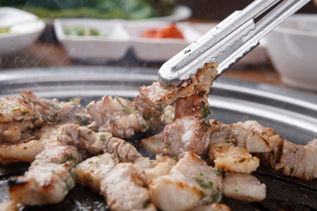 Pincers grabbing pork neck being grilled on iron grate