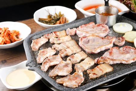 Pork neck being grilled on stone plate