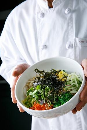 Hand picking up bowl with bibimbap Фото со стока