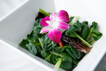 Spinach with flowers on china platter