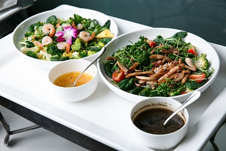 Various salad on round china platter, in buffet background