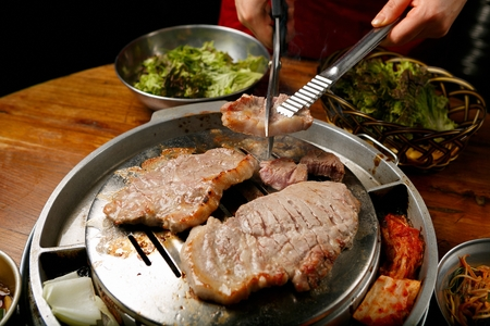 Pincers and scissors cutting pork neck being grilled on stainless grill