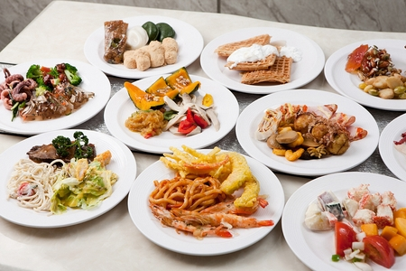 Various buffet food on plates, on white table