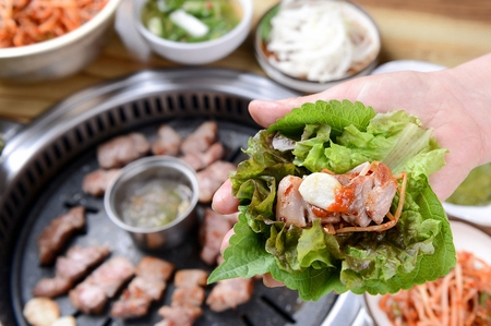 Hand grabbing pork neck being grilled on stone plate