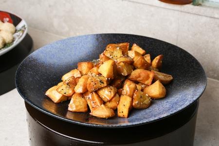 Deep-fried sugar glazed sweet potato wedges on plate