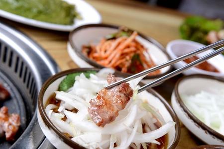 Chopsticks grabbing pork neck being grilled on stone plate, with seasoned onions 版權商用圖片