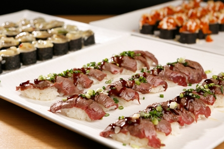 Beef sushi with sprinkled barbecue sauce and sliced chives on china platter Stock Photo