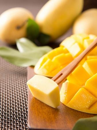 Wooden fork grabbing sliced mango from cutting board