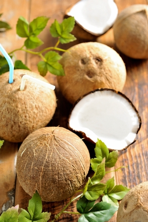sliced and whole coconuts, and coconut with straw